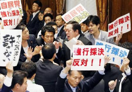 Yasukazu Hamada committee chairman (center) is surrounded by opposition politicians shouting and waving placards in protest against the special security bill.